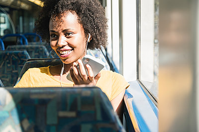 Happy young woman with earphones and smartphone on a train - p300m2155860 by Uwe Umstätter