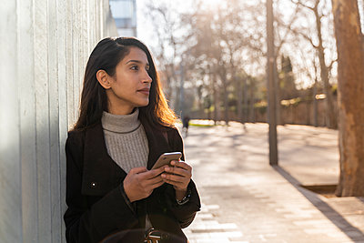 Young woman with smartphone in the city looking around - p300m2166215 by VITTA GALLERY