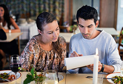 Friends reading menu at restaurant table - p426m747372f by Maskot