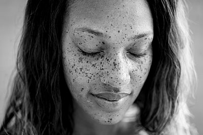 Portrait of freckled woman with eyes closed - p924m1422717 by Raphye Alexius