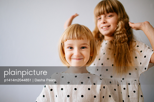 Two girls in polka dot dresses  - p1414m2044851 by Dasha Pears