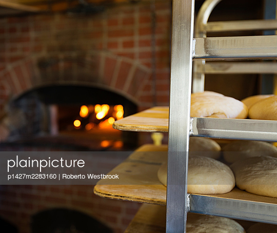 Artisan bread on shelves in kitchen with brick oven - p1427m2283160 by Roberto Westbrook