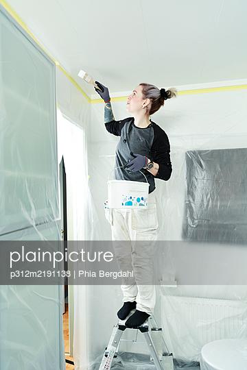 Woman painting ceiling - p312m2191138 by Phia Bergdahl