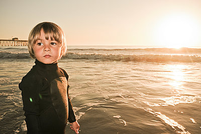 portrait of a little boy in a wetsuit at the beach in sunset light looking away - p1014m993697 by Kristianne Koch Riddle