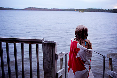 Rear view of girl wrapped in towel standing on jetty over lake - p1166m1229471 by Cavan Images