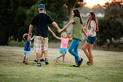 Family playing ring-around-the-rosy at park - p1166m1530902 by Cavan Images