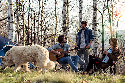 Friends camping in forest with man playing guitar - p300m1505778 by ZoneCreative