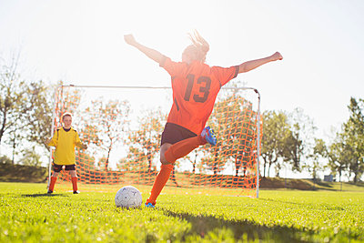 Young female soccer player about to kick soccer ball. - p328m783946f by Hero Images