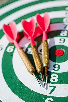 Darts lying on a dartboard - p4266818f by Tuomas Marttila