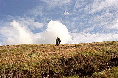 Man walking on hillside - p4296231 by Lilian Henglein