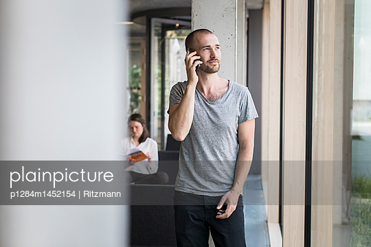 Young man using smartphone - p1284m1452154 by Ritzmann