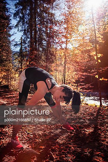 Woman jogging in autumn forest, stretching for warm up - p300m2166657 von Studio 27