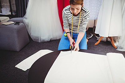 Female fashion designer cutting a white fabric - p1315m1199733 by Wavebreak