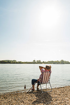Germany, Ludwigshafen, back view of senior man rrlaxing on folding chair at riverside - p300m1188813 by Uwe Umstätter