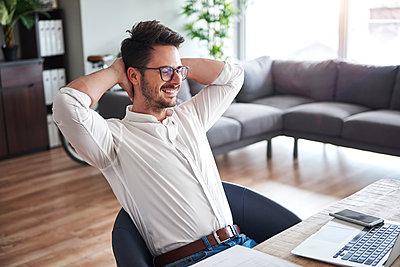 Content businessman sitting at desk  at home office - p300m2012200 von gpointstudio