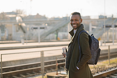 Portrait of smiling man with reusable cup waiting for the train - p300m2154612 by Hernandez and Sorokina