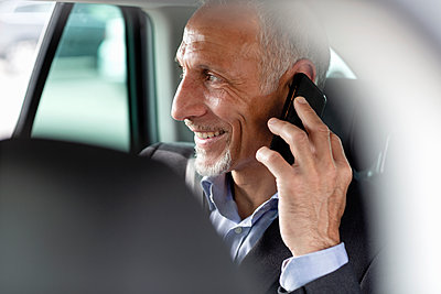 Male professional talking on smart phone while sitting in car - p300m2287339 by Emma Innocenti