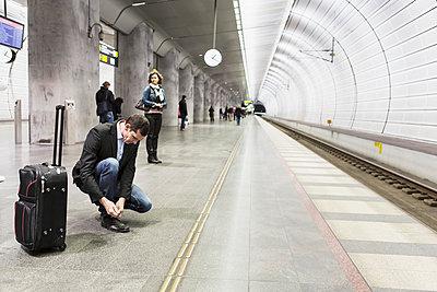Businessman tying shoelace while waiting at railway station - p426m1085304f by Kentaroo Tryman