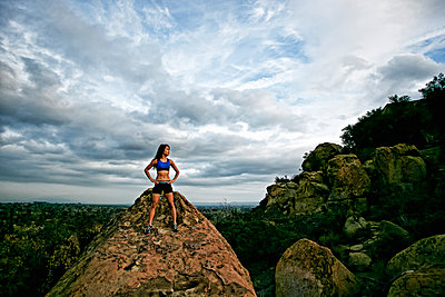 Vietnamese woman standing on rocky hilltop - p555m1412741 by Peathegee Inc