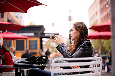 Thoughtful woman holding coffee cup while sitting at sidewalk cafe in city - p1166m1097194f by Cavan Images