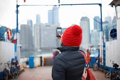 Woman photographing skyline with smartphone, Toronto, Canada - p429m1417880 by Peter Muller