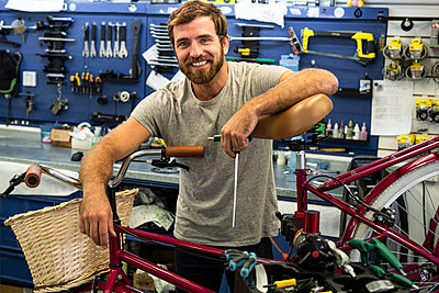 Mechanic leaning on bicycle - p623m2214733 by Frederic Cirou
