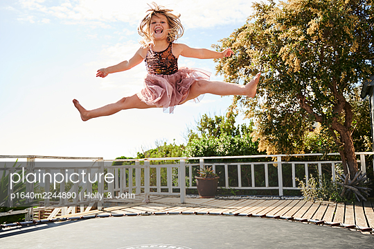 Little girl jumping on trampoline - p1640m2244890 by Holly & John