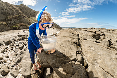 Curious child wearing snorkel looking in bucket - p1166m2138203 by Cavan Images