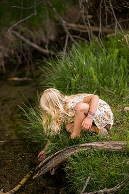 Blonde girl reaching into a stream with long grass - p1166m2292561 by Cavan Images