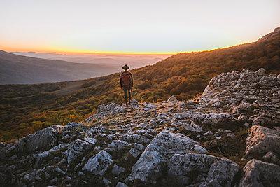 Man on rock by mountains at sunset - p1427m2163672 by Oleksii Karamanov