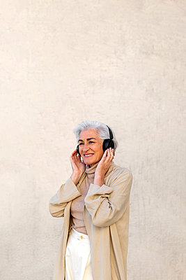 Contemplating mature woman smiling while listening music through headphones in front of wall - p300m2281468 by PICUA ESTUDIO