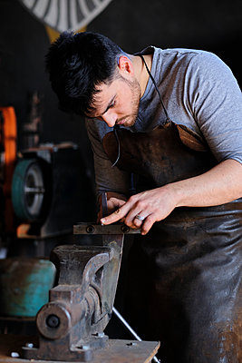 Young male blacksmith working on machine at workshop - p300m2281473 by Antonio Ovejero Diaz