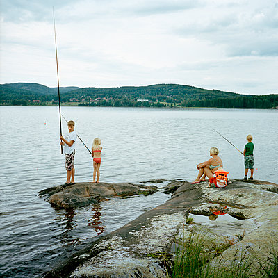 Children with mother fishing in lake - p528m1075409f by Johan Willner