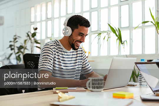 Laughing young man wearing headphones using laptop at desk in office - p300m1587533 von Bonninstudio