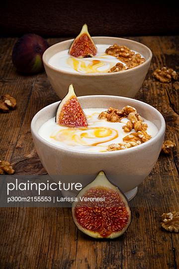 Bowls of Greek yogurt with honey, walnuts and fig - p300m2155553 by Larissa Veronesi