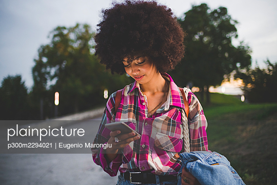 Young woman with afro hairdo using smartphone outdoors at dusk - p300m2294021 by Eugenio Marongiu