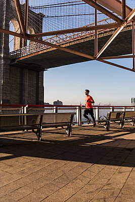 USA, New York City, man running at East River under Brooklyn Brige - p300m1192268 by Uwe Umstätter
