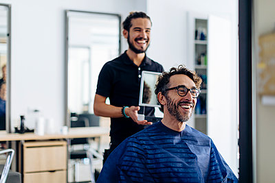 Happy hairdresser showing haircut to client in mirror at salon - p300m2203032 by Sofie Delauw