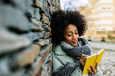 Smiling Afro woman writing in book while leaning on stone wall during winter - p300m2256849 by Xavier Lorenzo