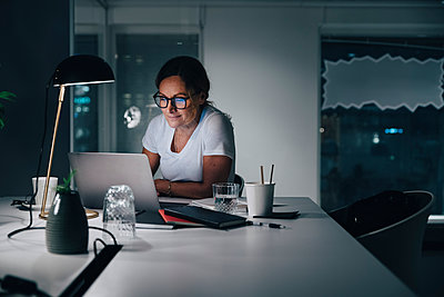 Confident businesswoman using laptop while working late night in office - p426m2194753 by Maskot