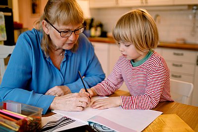 Grandmother assisting grandson in studying at home - p426m2195089 by Maskot