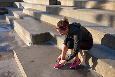 Young woman tying shoelace on training shoe, stretching legs - p429m1557471 by Gonçalo Barriga