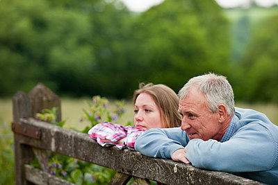 Father and daughter on wooden fence - p429m712139f by Colin Hawkins