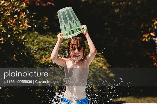 Boy standing pouring bucket of water over his own head - p1166m2255836 by Cavan Images