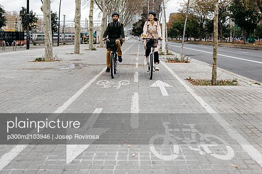 Couple riding e-bikes in the city on bicycle lane - p300m2103946 by Josep Rovirosa