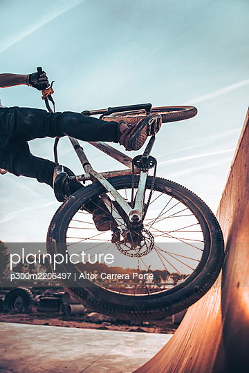 Young man riding bicycle on ramp in park during sunset - p300m2206497 by Aitor Carrera Porté