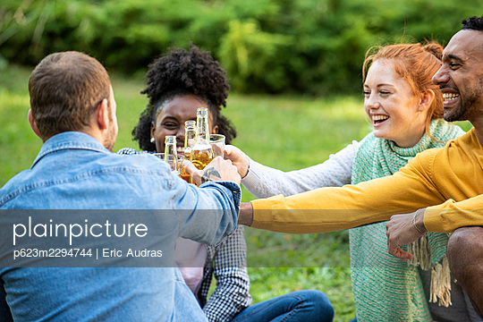 Happy young friends toasting drinks in garden - p623m2294744 by Eric Audras