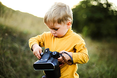 Boy  with camera while standing on grassy field - p1166m2095996 by Cavan Images