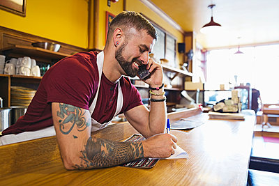Male deli owner taking order by phone - p1192m1043757f by Hero Images