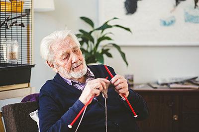 Senior man knitting while sitting in nursing home - p426m2018630 by Maskot